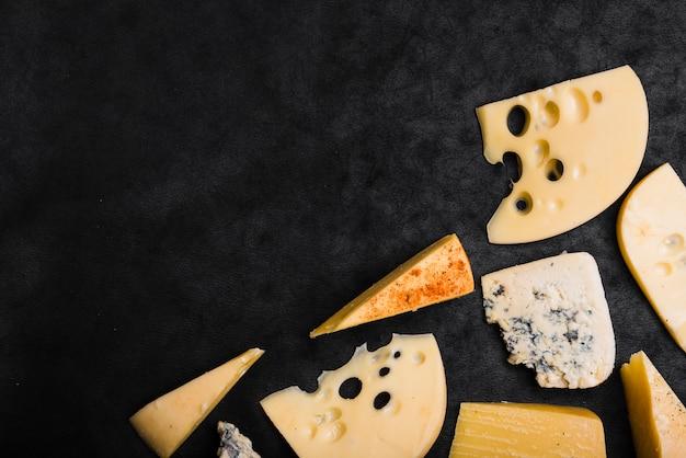 Maasdam; cheddar; queijo gouda e azul sobre fundo preto Foto gratuita