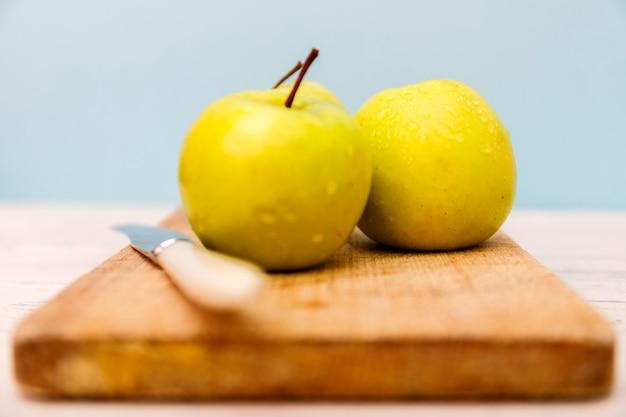 Maçã amarela na mesa de madeira. maçã verde e faca na mesa de madeira. Foto Premium