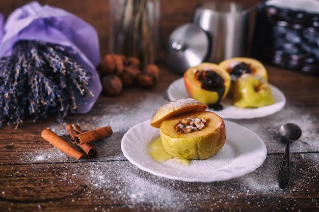 Maçã assada recheada com nozes, mel e chocolate em pratos de sobremesa branco, fundo escuro de madeira. doce de natal. conceito de alimentação saudável. Foto Premium