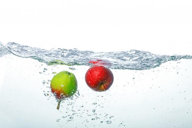 Maçã caindo em água limpa Foto Premium