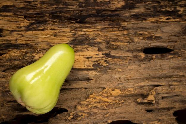 Maçã cor-de-rosa verde em de madeira. sombrio Foto Premium