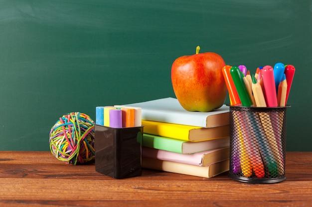 Maçã e livros com lápis e quadro-negro Foto Premium