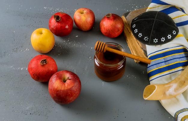 Maçã e mel, comida tradicional do livro de torá do ano novo judaico rosh hashana, kippah yamolka talit Foto Premium