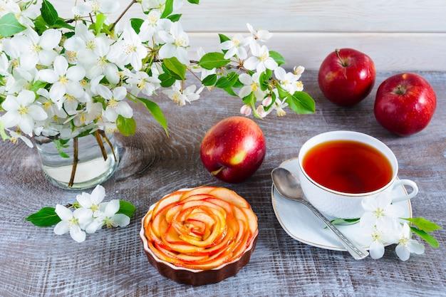 Maçã em forma de torta de rosas e chá na mesa de madeira Foto Premium