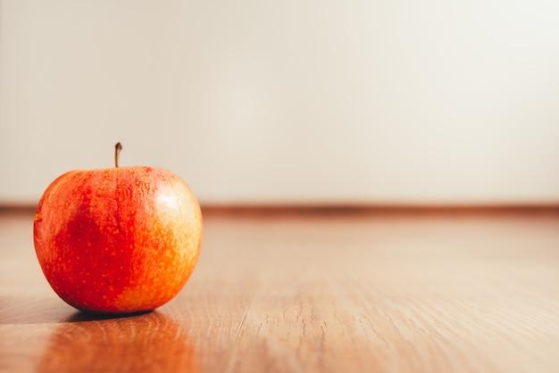 Maçã madura isolada no fundo branco e no assoalho de madeira, conceito da dieta para perder o peso no verão. Foto Premium