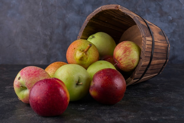 Maçã, pêssego e peras em um balde de madeira Foto gratuita