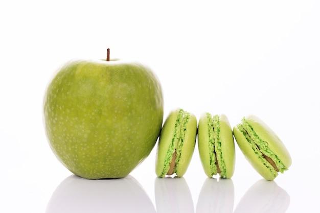 Maçã verde com macaroons em fundo branco Foto gratuita