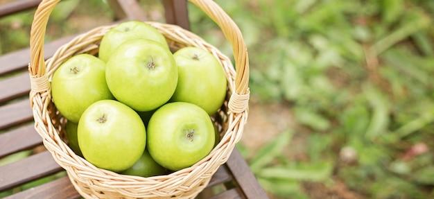 Maçã verde, em, cesta vime, ligado, cadeira jardim, grama verde, tempo colheita, espaço cópia Foto Premium