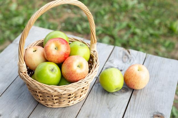 Maçã verde na cesta de vime na mesa de madeira grama verde no jardim tempo de colheita estilo rústico Foto Premium