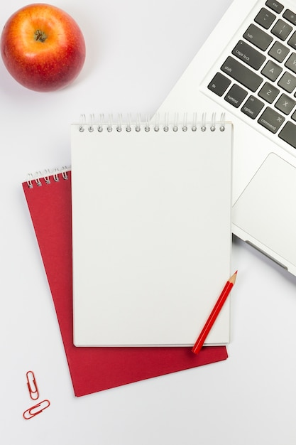 Maçã vermelha, bloco de notas espiral em branco, lápis de cor vermelha no laptop sobre fundo branco Foto gratuita