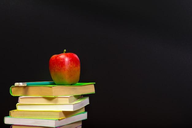 Maçã vermelha e livros antigos na mesa de madeira Foto Premium