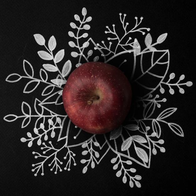 Maçã vermelha sobre contorno floral mão desenhada Foto gratuita