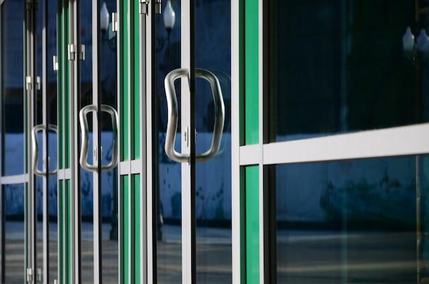 Maçaneta da porta cromada e vidro da fachada de escritório em alumínio moderno Foto Premium