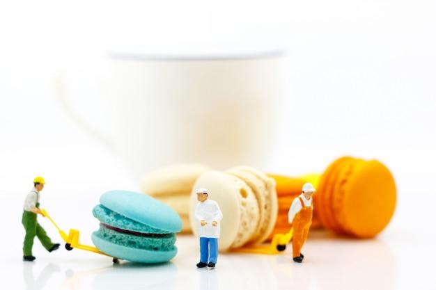 Macaron de movimento de trabalhador em miniatura com uma xícara de café. Foto Premium