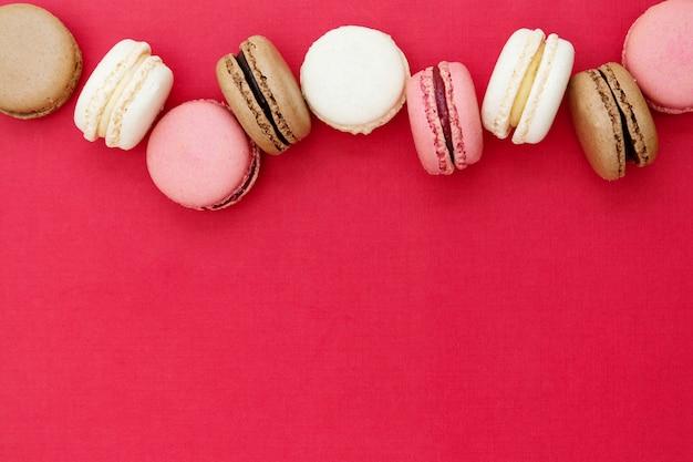 Macarons bolos ou biscoitos sobre fundo vermelho. postura plana. copie o espaço. Foto Premium