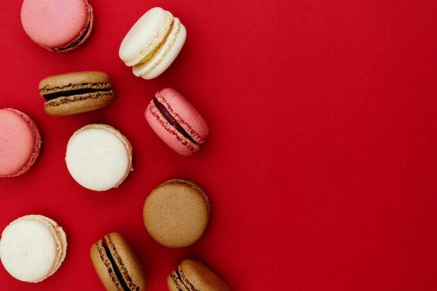 Macarons bolos sobre fundo vermelho. postura plana. copie o espaço. Foto Premium