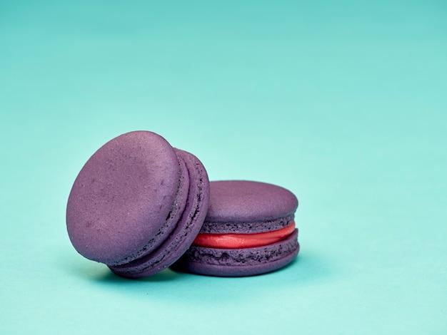 Macarons coloridos em um fundo azul Foto Premium