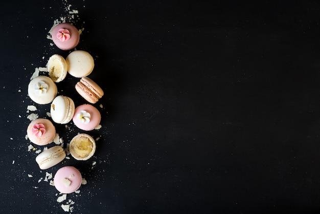 Macarons coloridos no fundo de pedra preto. vista superior com espaço de cópia. Foto Premium