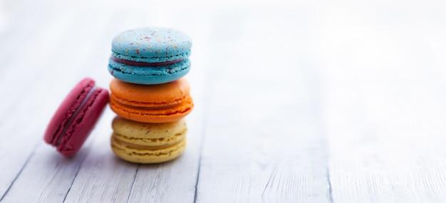 Macarons franceses. pilha de biscoito colorido na mesa de madeira, copyspace Foto Premium
