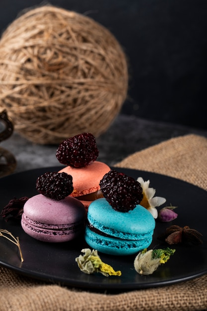 Macarons franceses tricolor em um pires preto Foto gratuita