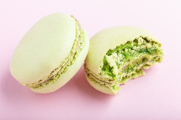 Macarons verdes inteiros e mordidos ou bolos de confeitos em fundo rosa pastel Foto Premium