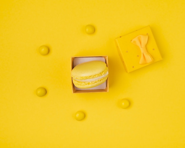 Macaroon na caixa de presente toda amarela vista superior Foto gratuita