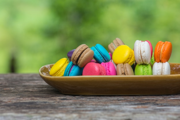 Macaroons coloridos no prato na mesa de madeira Foto Premium