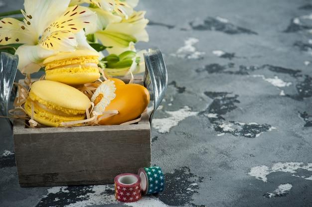 Macaroons de amarelos com coração em caixa Foto Premium