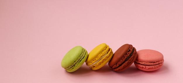 Macaroons de cookies francês colorido sobre fundo rosa, cópia espaço, foto horizontal Foto Premium