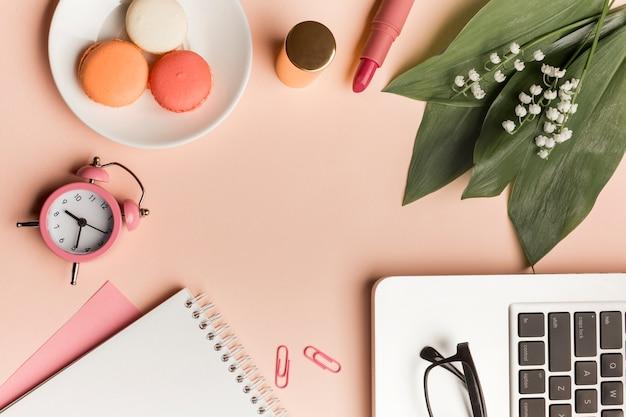 Macaroons, despertador, batom, folhas e flor com o bloco de notas em espiral e laptop Foto gratuita