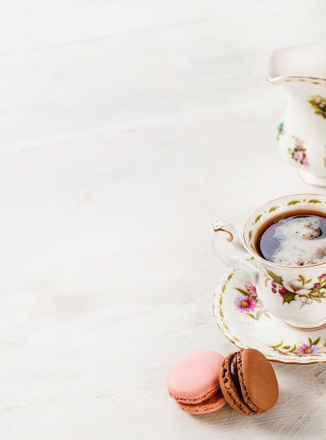 Macaroons e cerâmica xícara de café sobre fundo de madeira Foto gratuita