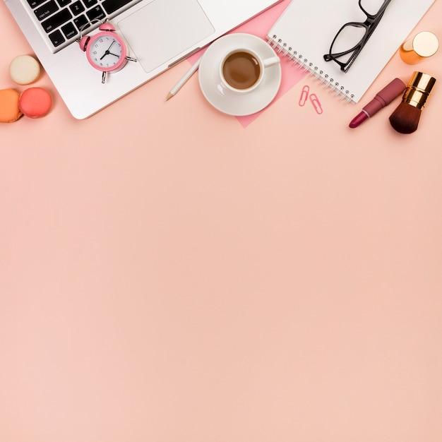 Macaroons, pincéis de maquiagem com despertador no laptop e artigos de papelaria no cenário de pêssego Foto gratuita