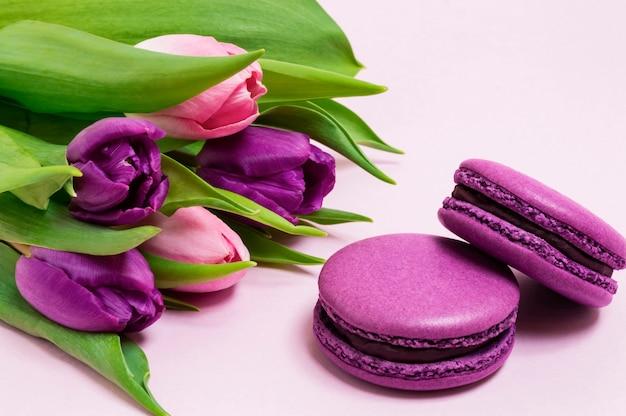 Macaroons roxos, buquê de tulipas roxas e rosa sobre um fundo rosa claro Foto Premium