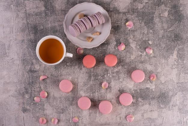 Macaroons saborosos rosa lindos sobre um fundo de concreto Foto Premium
