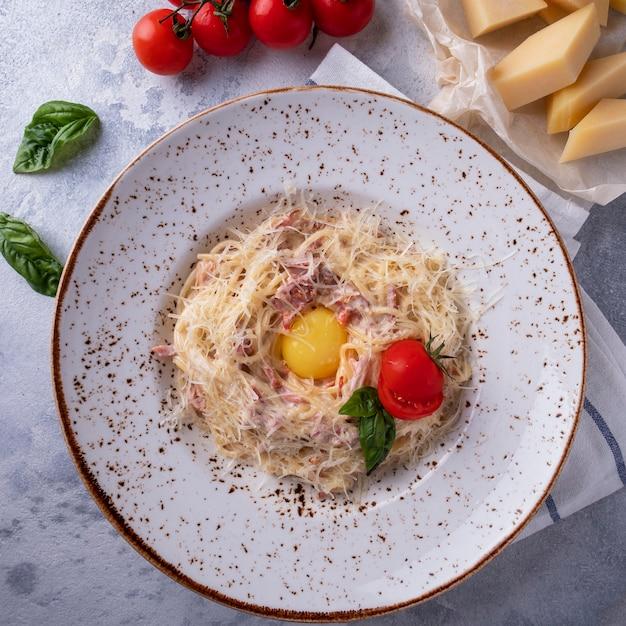 Macarrão à carbonara, ovo, queijo parmesão e molho de natas. vista do topo. fechar-se Foto Premium