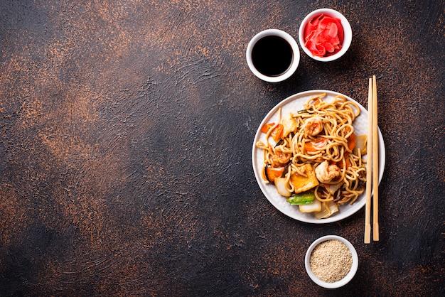 Macarrão asiático com camarão e legumes Foto Premium