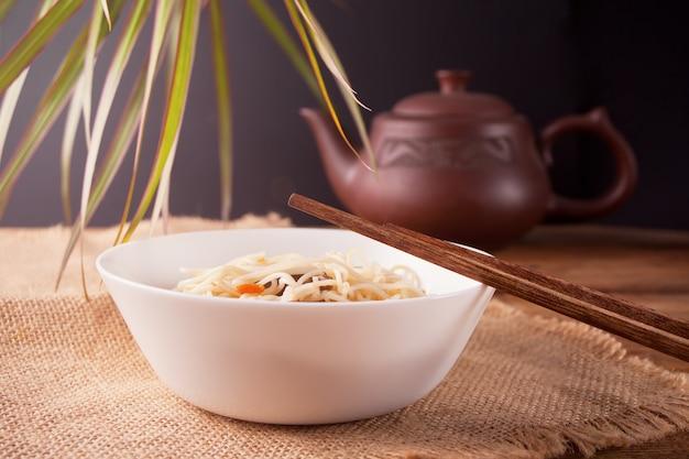 Macarrão asiático com carne, legumes na tigela com pauzinhos, fundo de madeira rústico. jantar de estilo asiático. macarrão japonês chinês Foto Premium