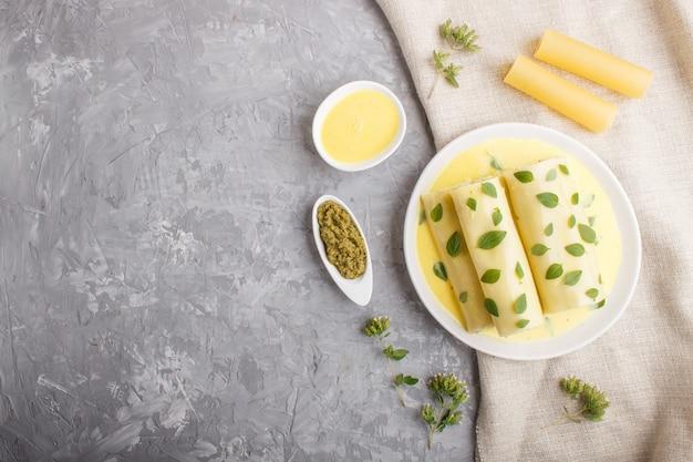 Macarrão canelone com molho de ovo, queijo creme e orégano folhas em um concreto cinza. Foto Premium