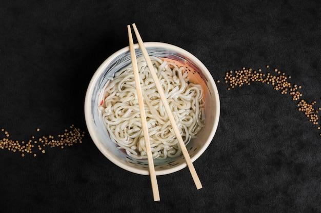 Macarrão caseiro de udon de comida japonesa com design de sementes de coentro em fundo preto Foto gratuita