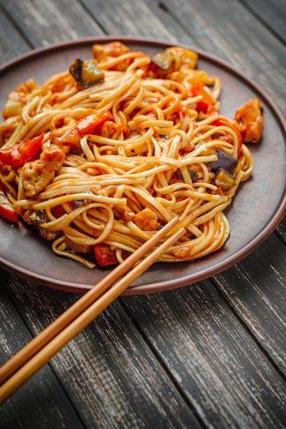Macarrão chinês em molho agridoce e pauzinhos na mesa Foto Premium