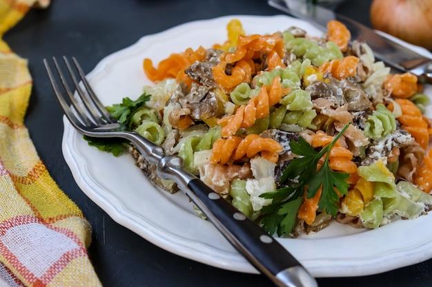 Macarrão colorido fusilli com legumes em um prato branco em foco seletivo, escuro Foto Premium