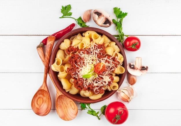 Macarrão com carne, molho de tomate e legumes em cima da mesa Foto Premium