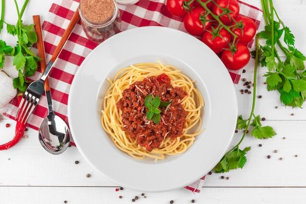 Macarrão com carne, molho de tomate e legumes na mesa Foto Premium