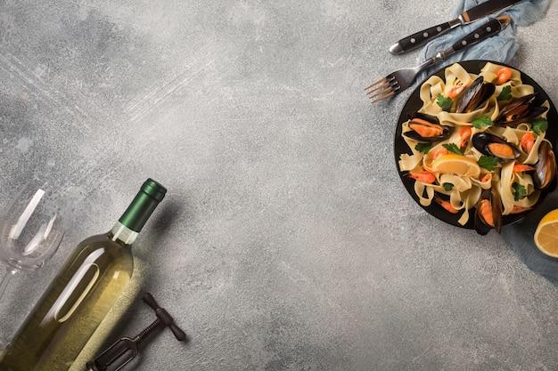Macarrão com frutos do mar e vinho branco na mesa de pedra. mexilhões e camarões vista do topo. Foto Premium
