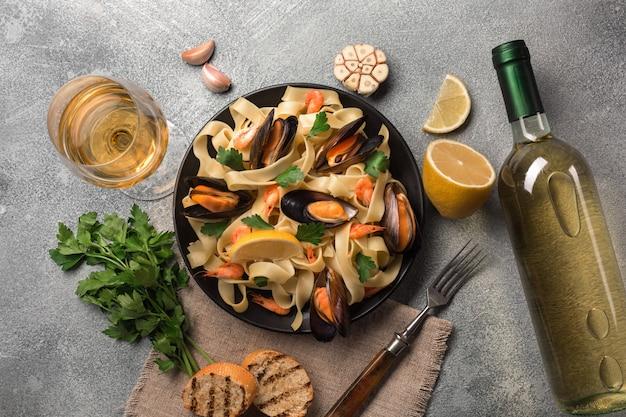 Macarrão com frutos do mar e vinho branco na mesa de pedra. mexilhões e camarões Foto Premium