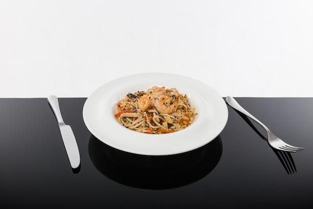 Macarrão com frutos do mar em uma mesa preta com um branco Foto Premium