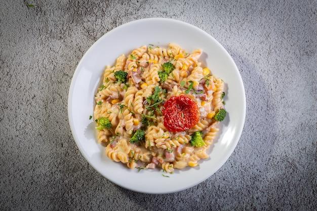 Macarrão com molho bechamel e legumes Foto Premium