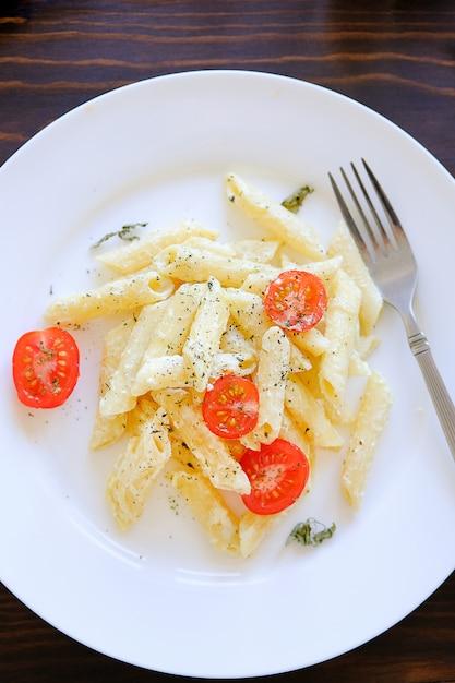 Macarrão com molho de creme, queijo, creme de leite, tomate, ervas e especiarias num prato branco sobre uma mesa de madeira. Foto Premium