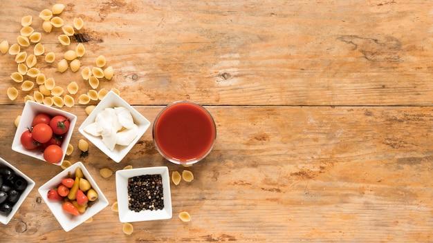 Macarrão conchiclioni cru; tigelas de tomate cereja; queijo mussarela; pimenta; azeitonas pretas; pimenta preta e molho sobre a mesa de madeira Foto gratuita