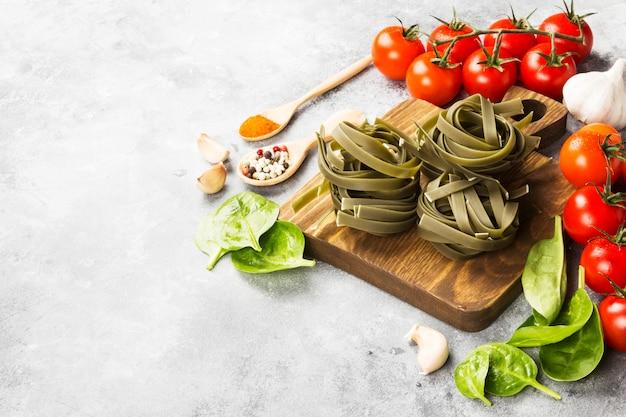 Macarrão cru de tagliatelle com espinafre e ingredientes para cozinhar Foto Premium